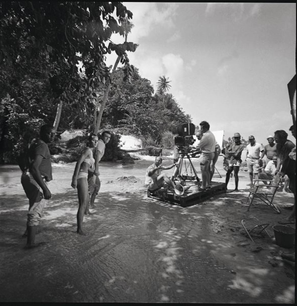 Terence Young positioned under the camera directing Sean Connery, Kitzmiller, Ursula Andress on location in Jamaica.