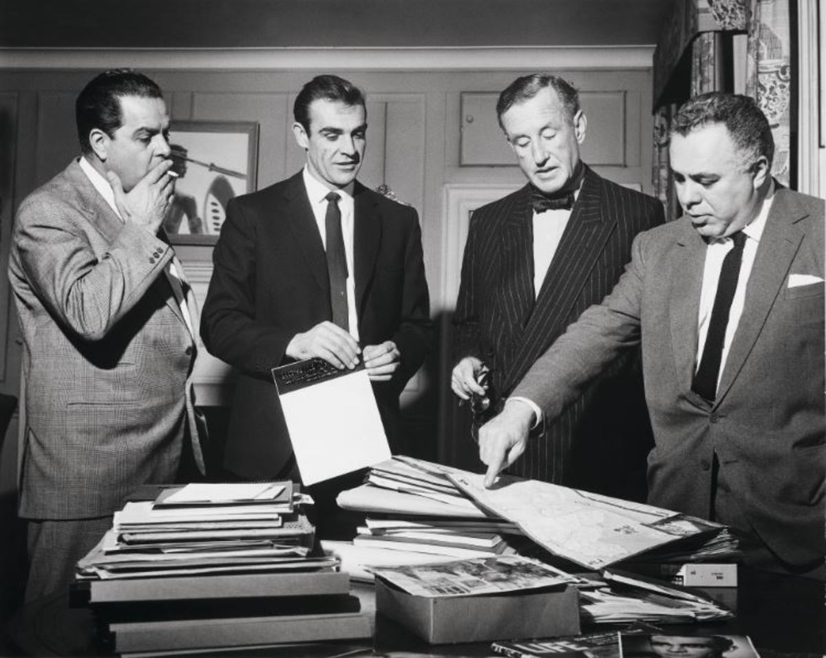 """During the filming preparation of """"Dr. No,"""" Cubby Broccoli, Sean Connery, Ian Flemming, and Harry Saltzman look at a map of Jamaica."""