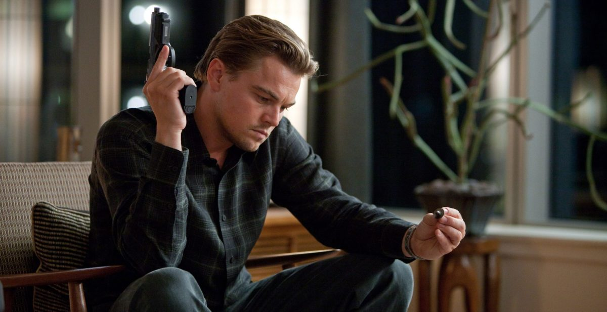 A ring-less Cobb examines his spinning top totem in Inception