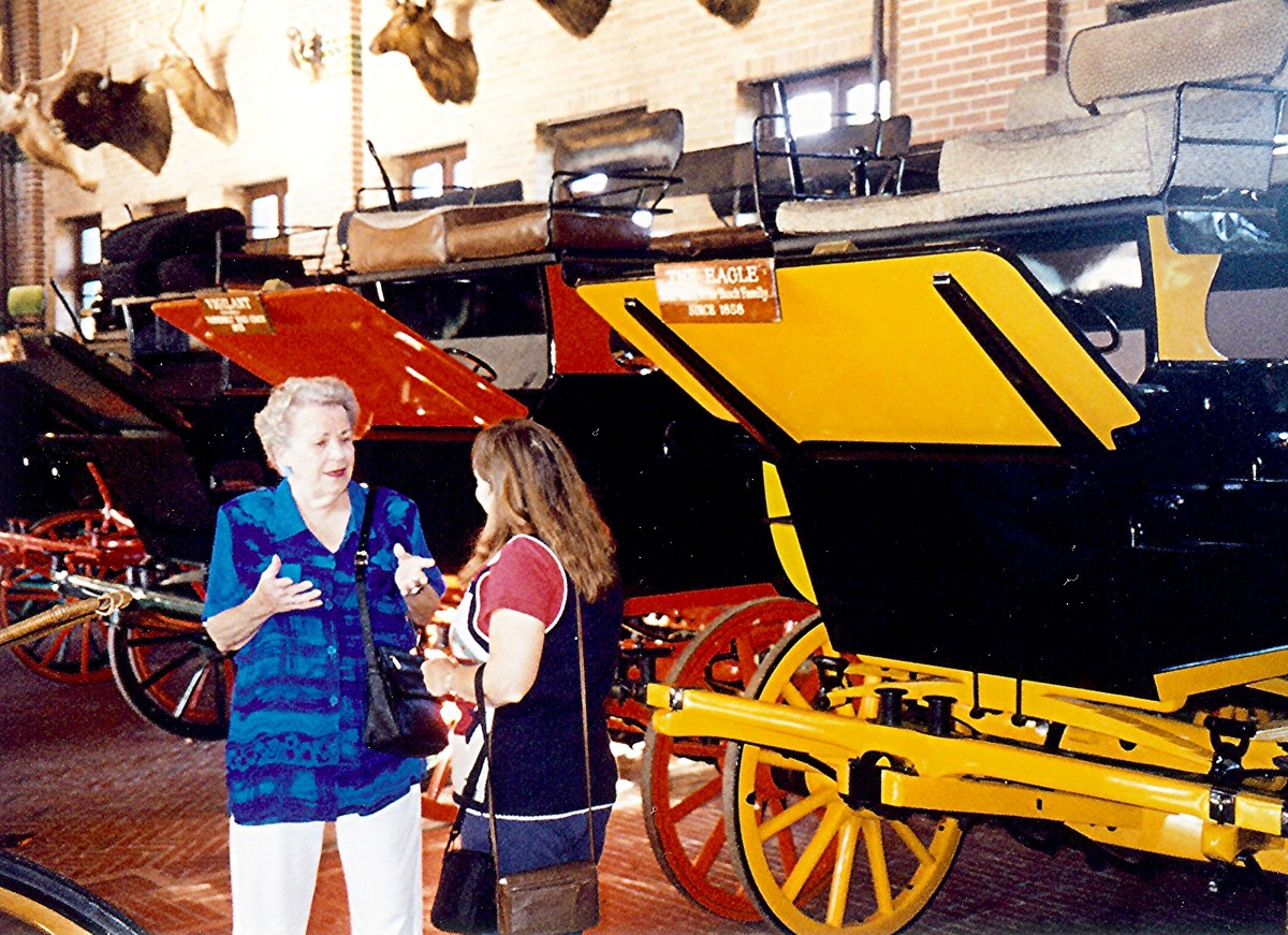 Inside the building showcasing the collection of old coaches and carriages.