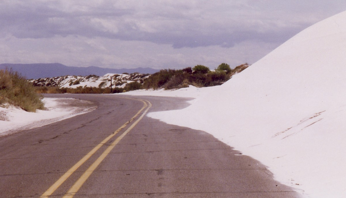 White sand encroaching upon the road.