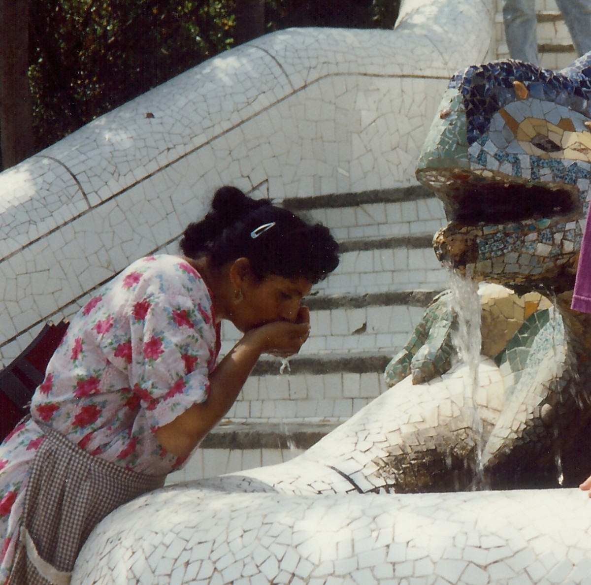 A woman drinking from the dragon fountain