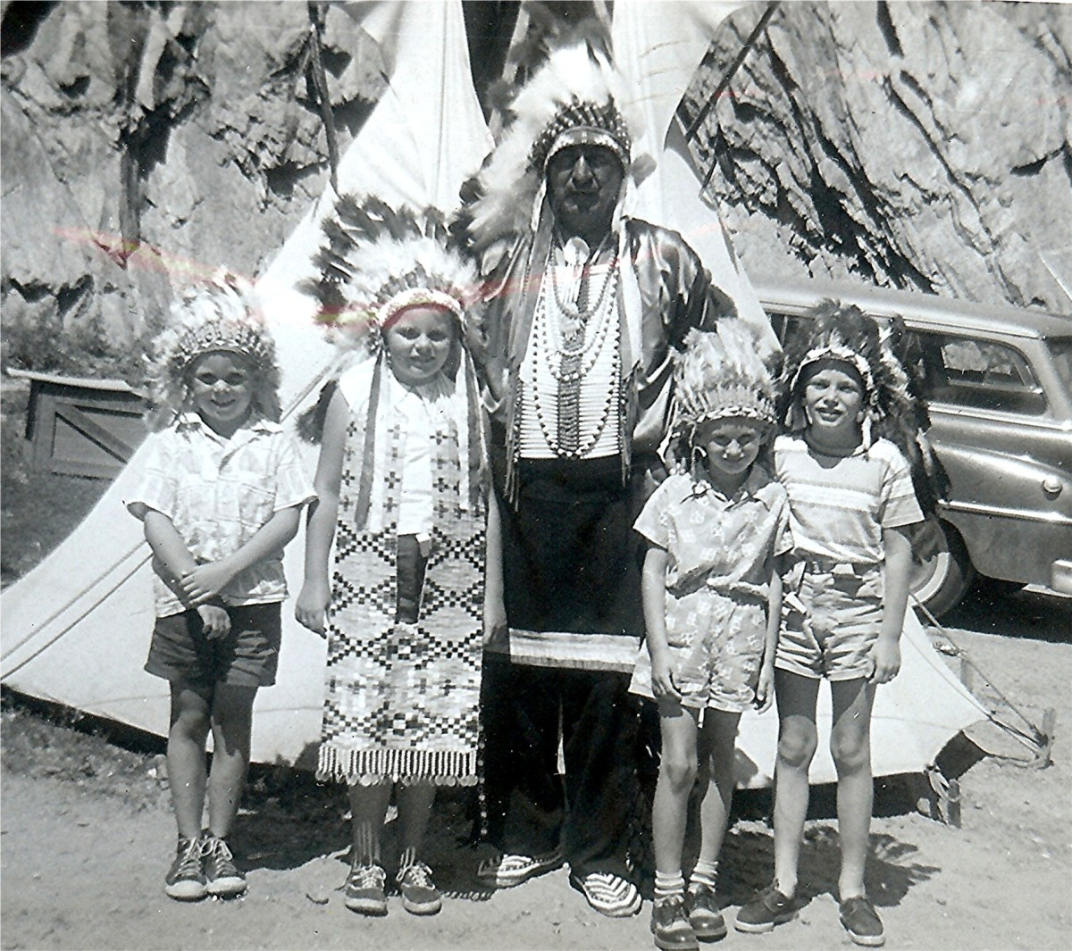 "Kids posing with American Indian in costume, 1950s (""Johnny - Peggy - Chief - Billy - Tommy"")"