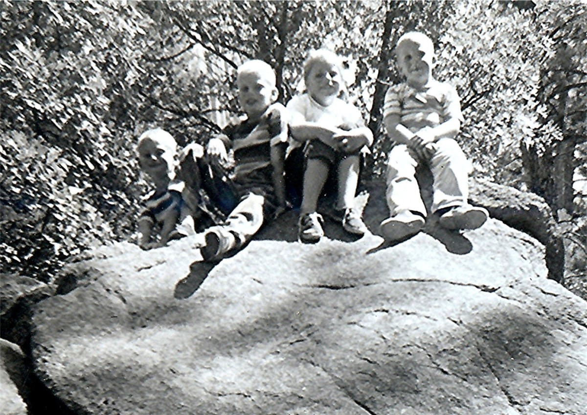 """Billy, Tommy, Peggy & Johnny on rock in park below Devils Tower"""