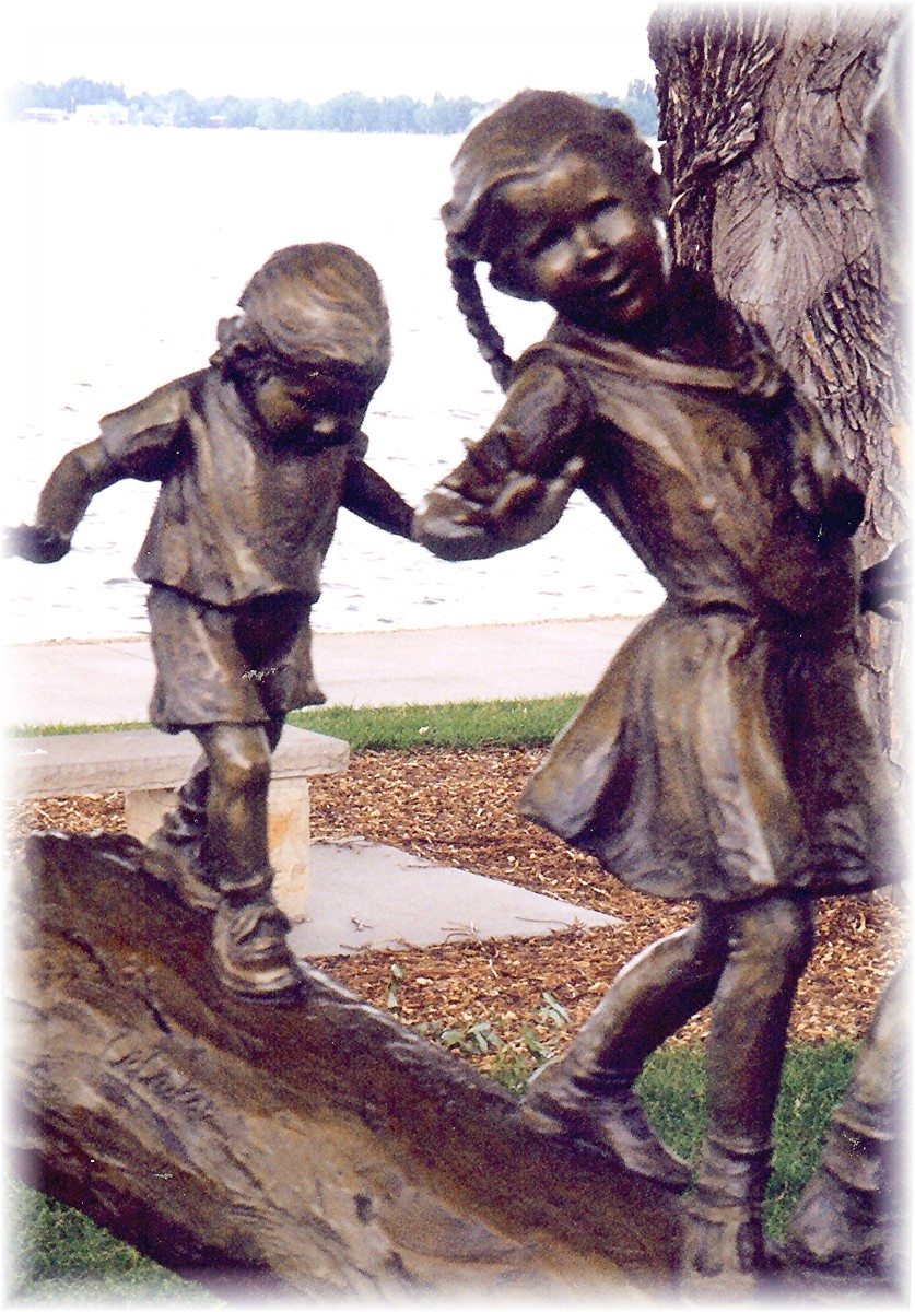 Partial view of a sculpture where 5 children are balancing themselves as they make their way across a log.