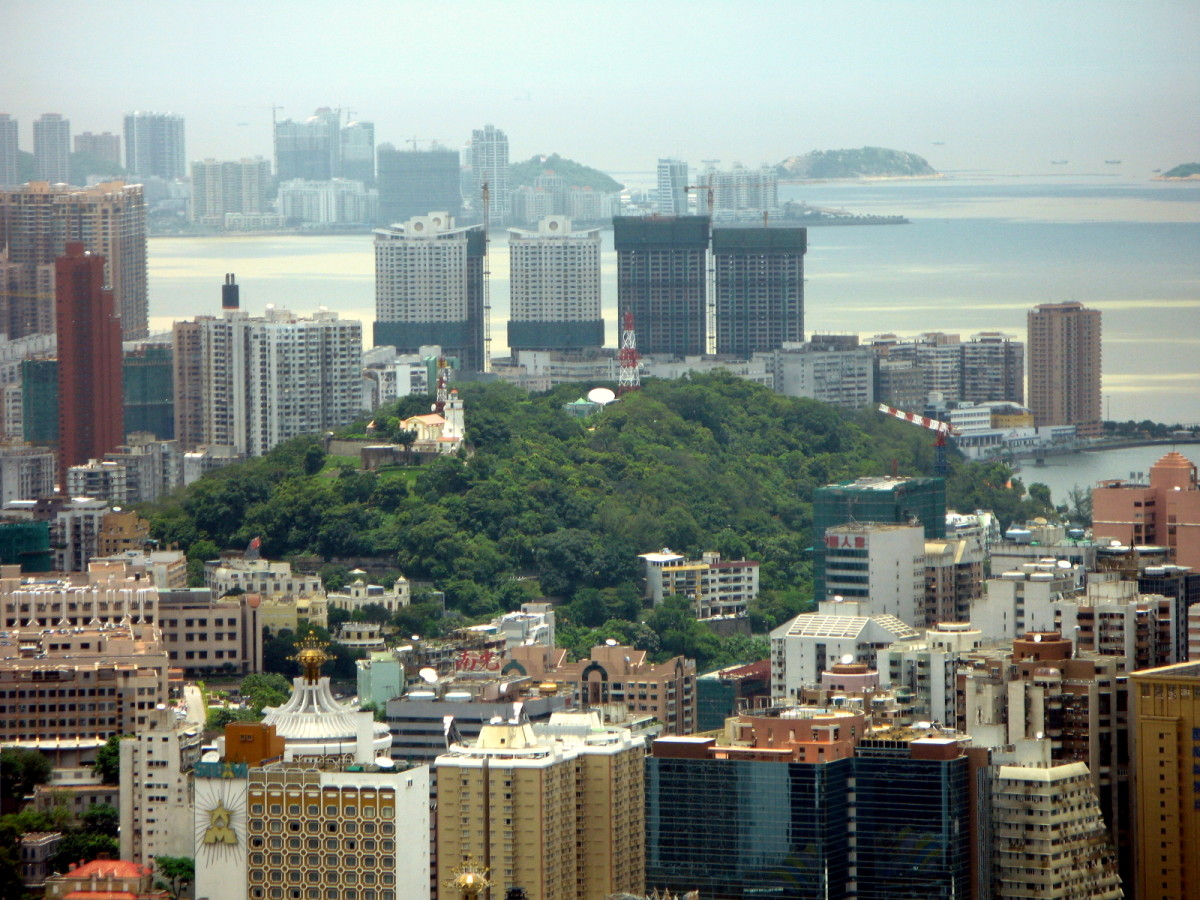 Guia Fort and lighthouse on green hill in photo's center contrasts Macau's old and new.