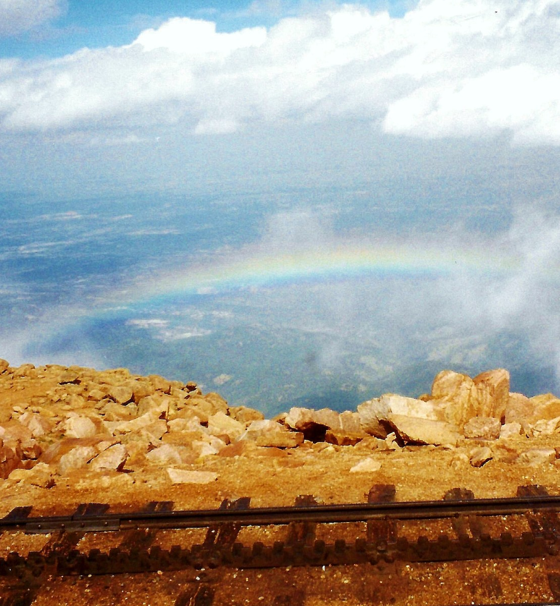 View of the cog railway track and beautiful rainbow at the top of Pikes Peak.