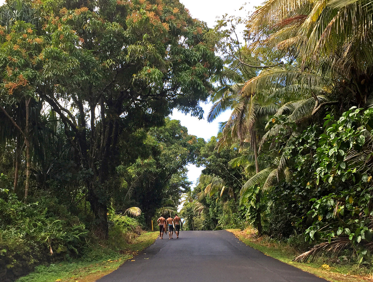 Surfers walk to Pohoiki Beach park.