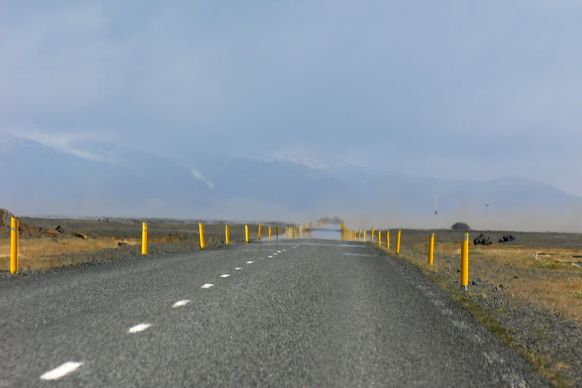 What appears to be water on the road ahead is merely a mirage.