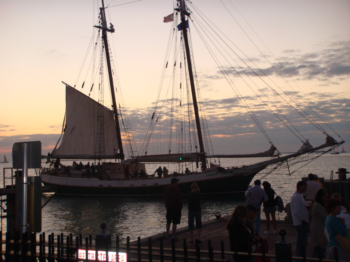 A schooner returning to harbor from a sunset sail