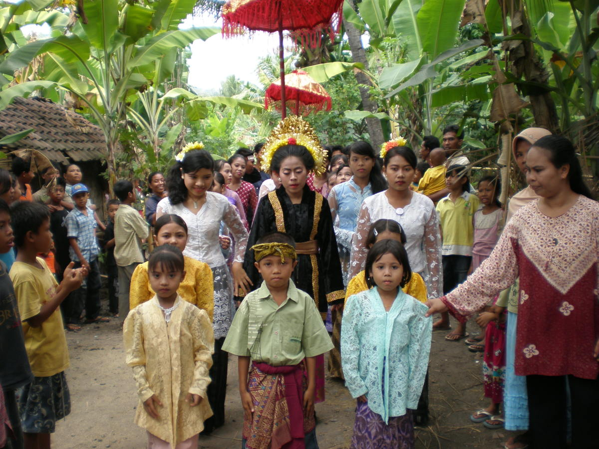 Traditional Indonesian Wedding, Lombok, Indonesia. Here you can see the procession walking through the jungle, headed by the bride (dressed in black with a golden headdress).