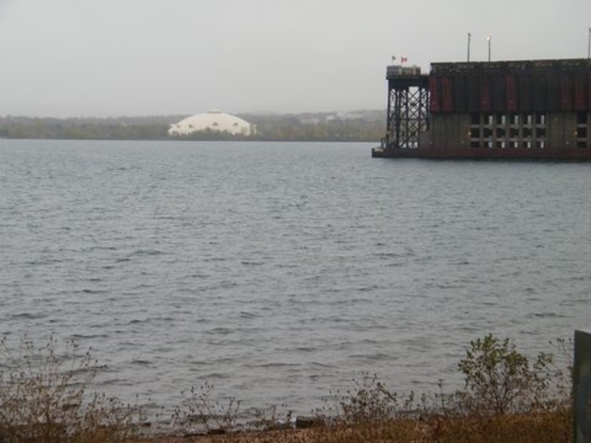 View from Presque Isle Park of Northern Michigan University Superior dome and of part of a working iron ore dock. Trains bring ore from a mine and ships take it away.