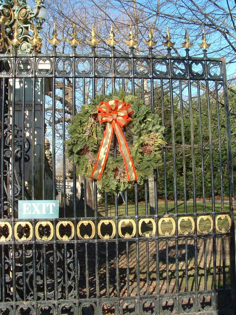 One of the iron gates marking the circular driveway, decorated with a large wreath for Christmas.