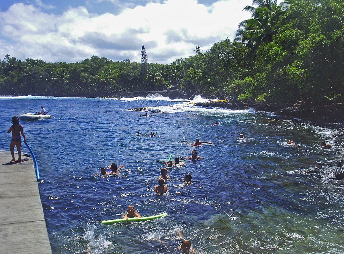 Swimming lagoon BEFORE the eruption, with clear blue water and happy swimmers.
