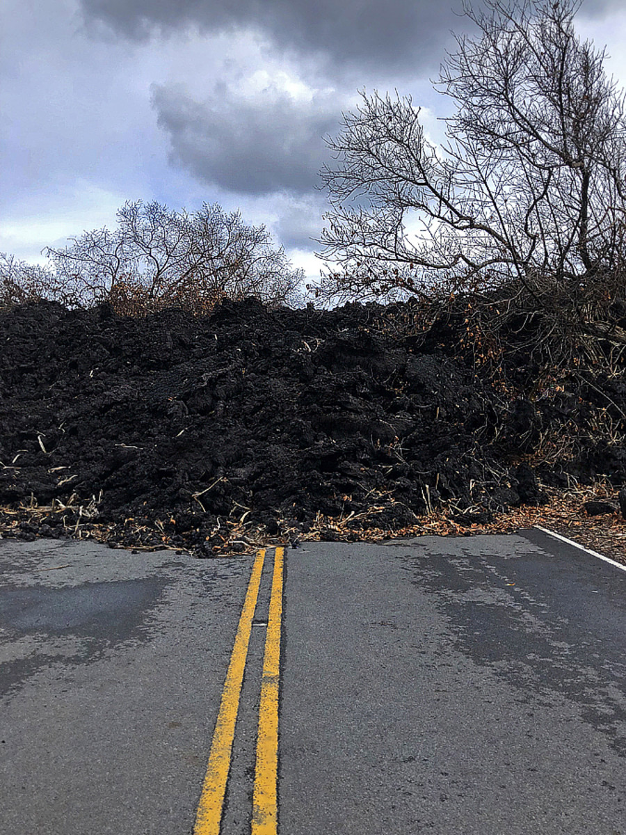 A wall of lava and burnt trees blocking the road.