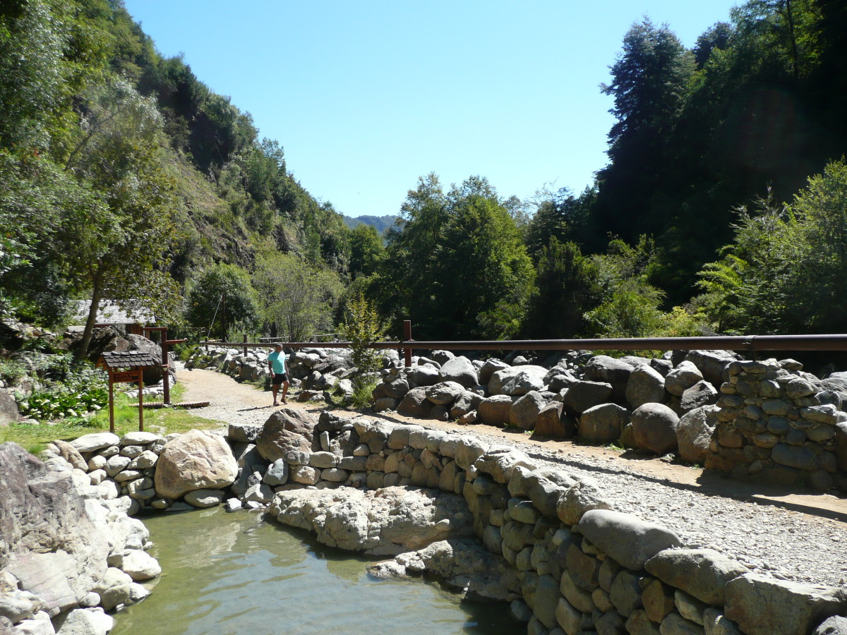 The natural appearance of the hot springs is retained at the Termas de Los Pozones.  The river is beyond the built up wall.