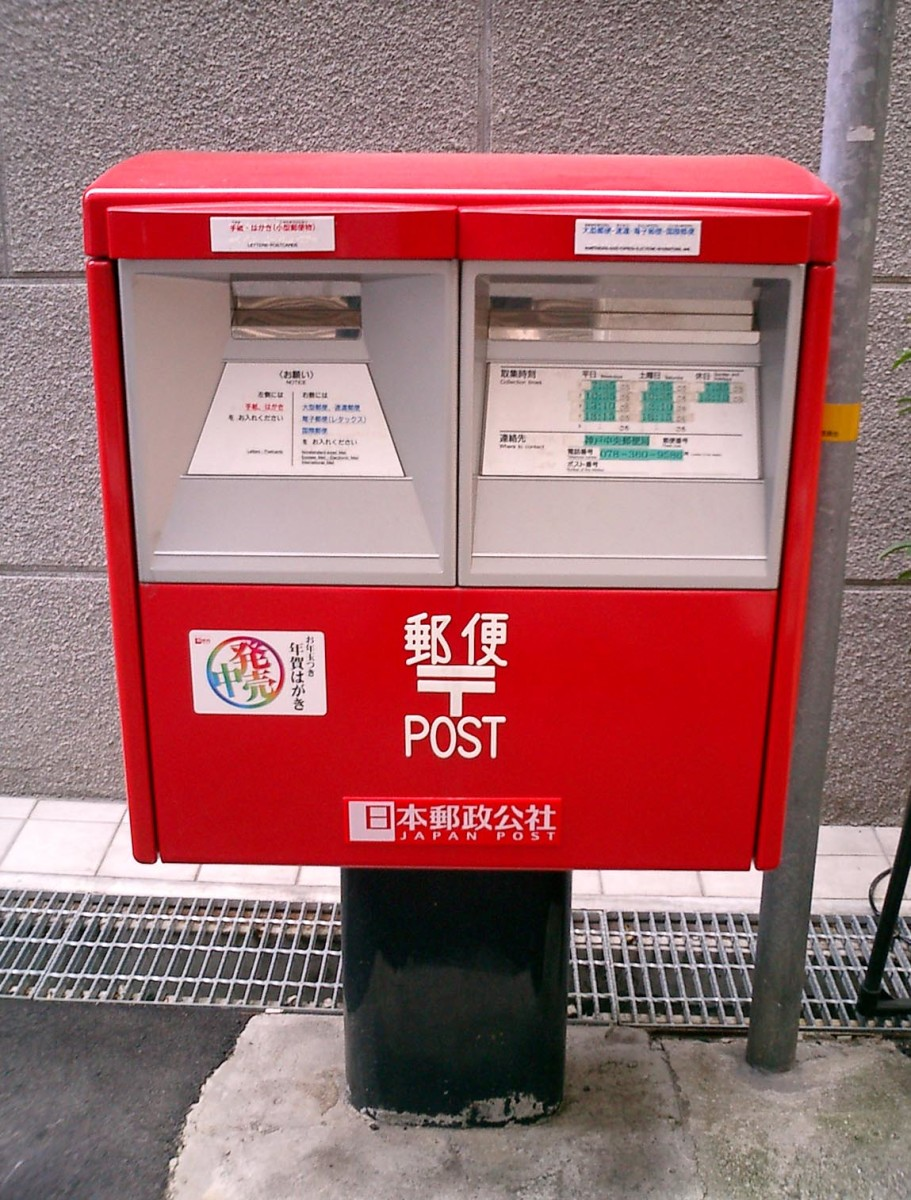 A standard public Japanese mailbox. The official color for the Japan Post is bright red.