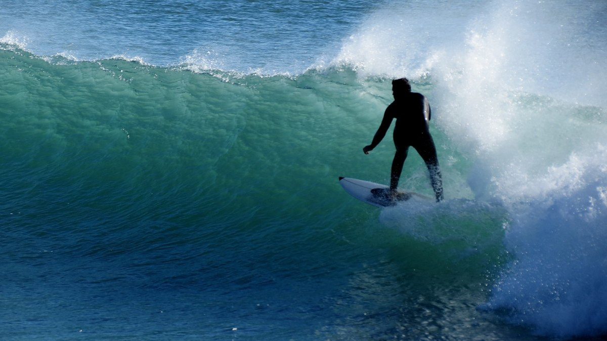 Portugal is known for its long, surfable coast. This image shows a surfer riding a wave at Praia da Poça near Estoril, Portugal.
