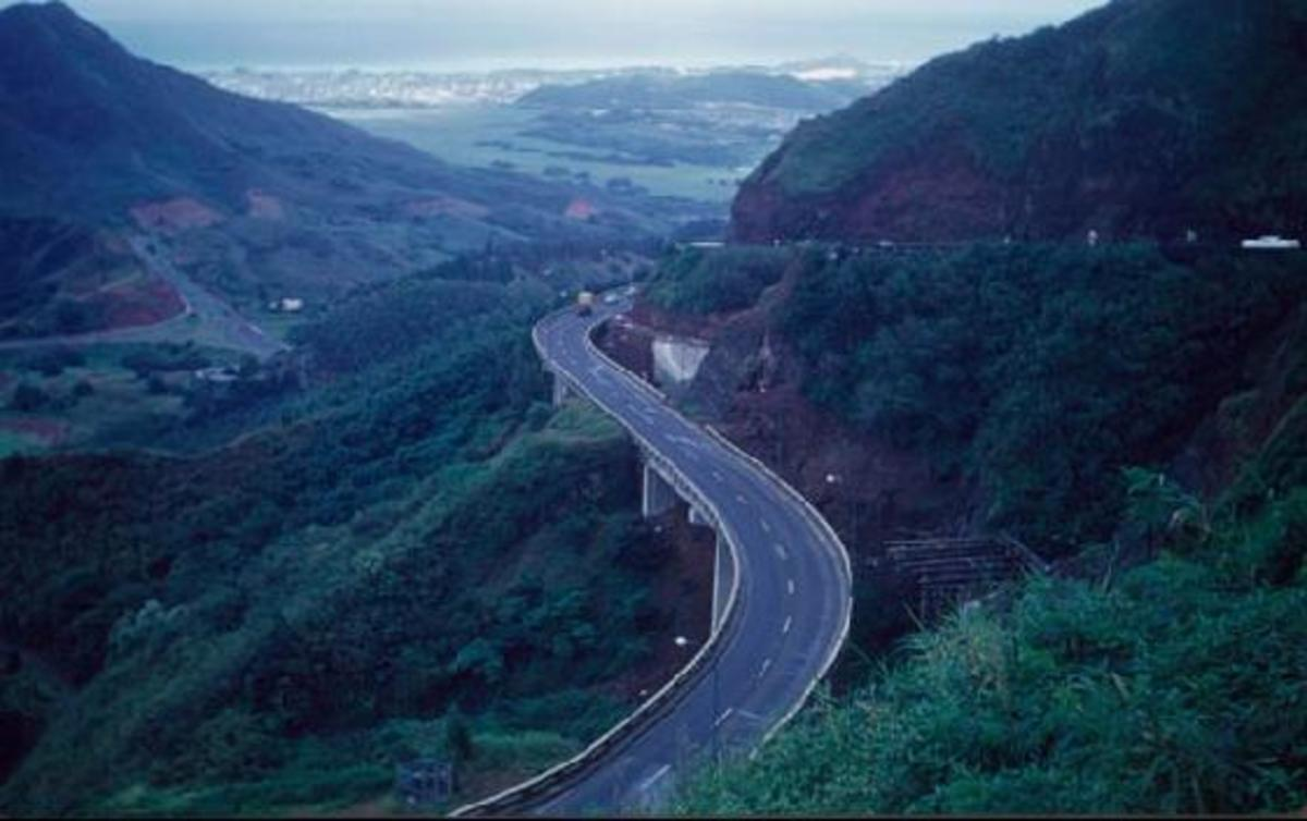 An aerial view of the highway to the windward side of O'ahu on the way to the North Shore, with Kane'ohe and the blue Pacific Ocean beyond.