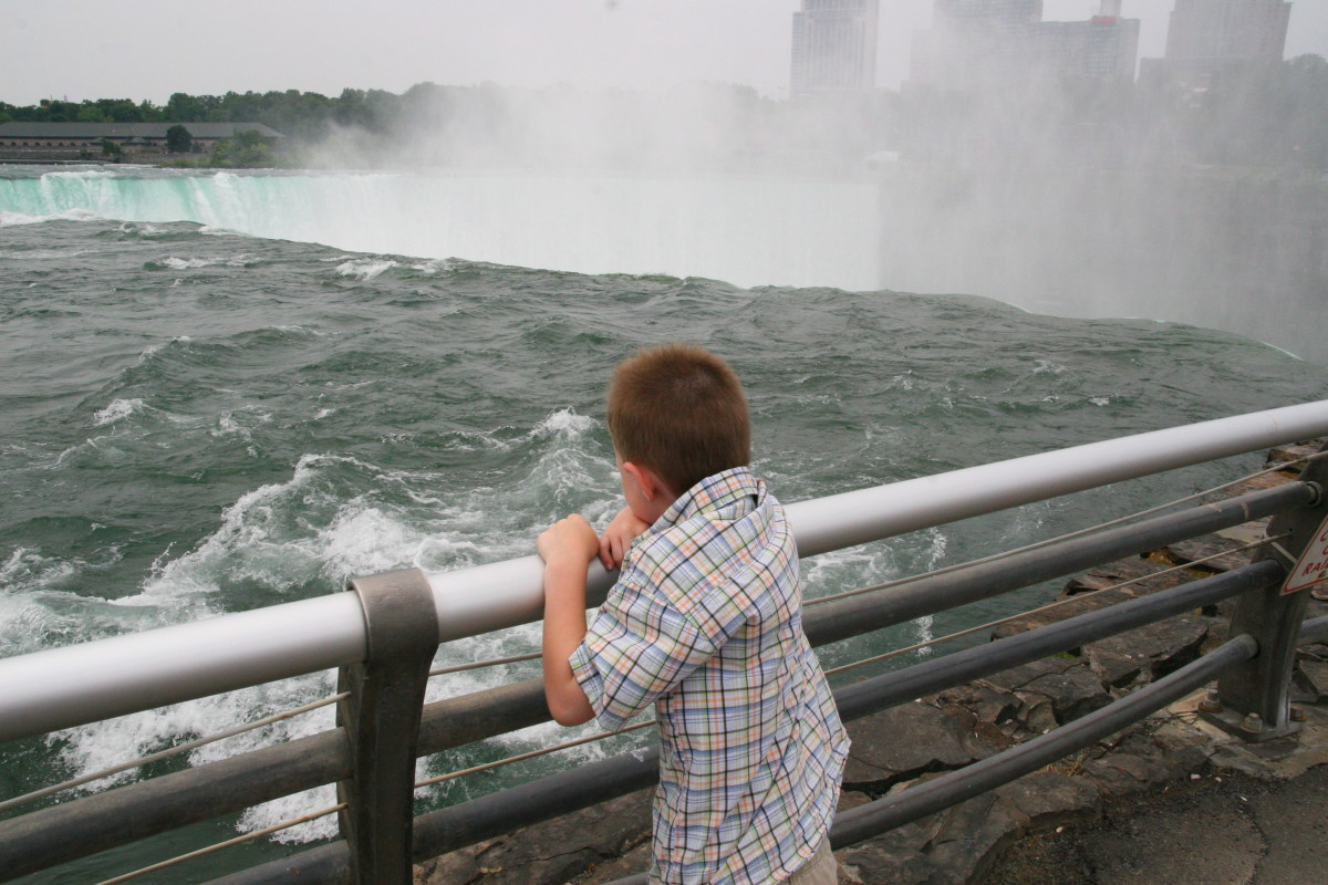 The author's son watches the water thunder past and topple over the precipice.