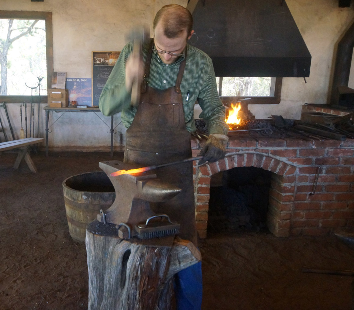 Blacksmith forging the spoon handle.
