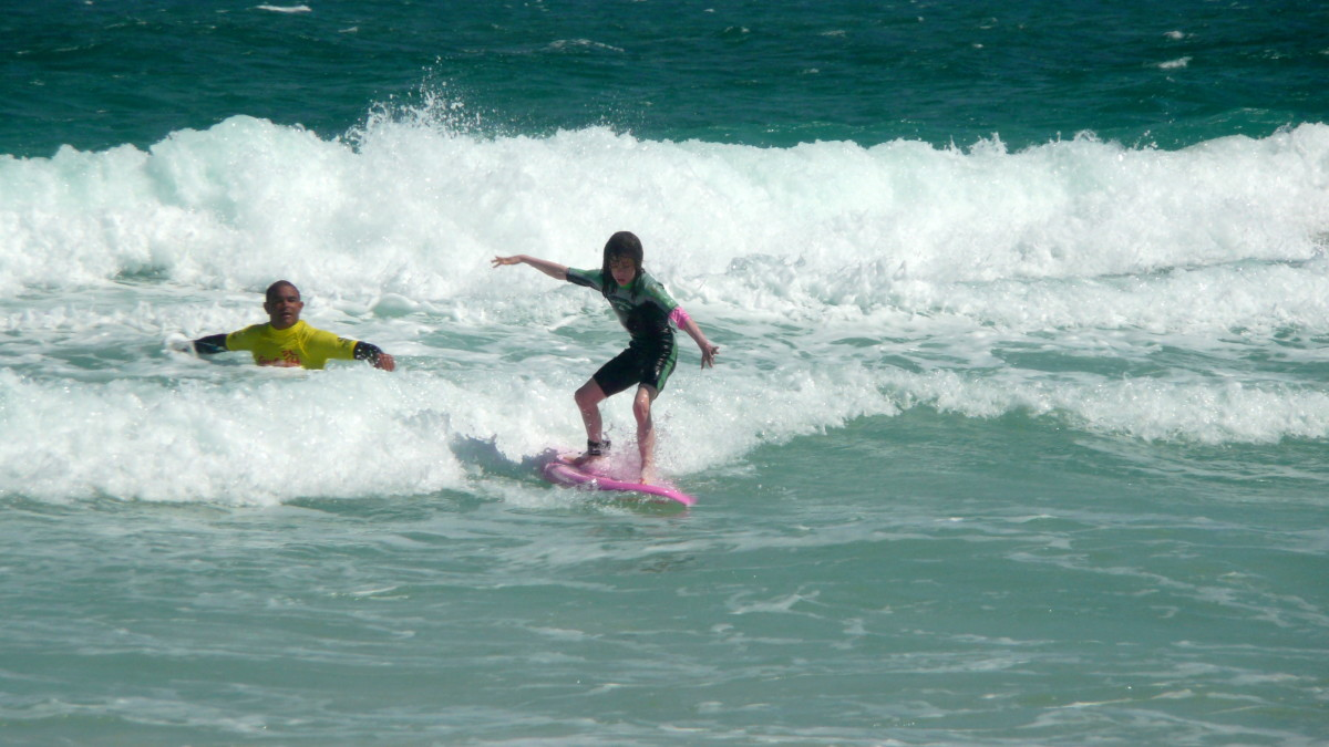 A surfing lesson, with the instructor close by