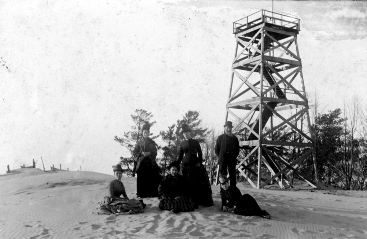 People on top of Mt. Baldhead in front of tower construction. Where are the trees?