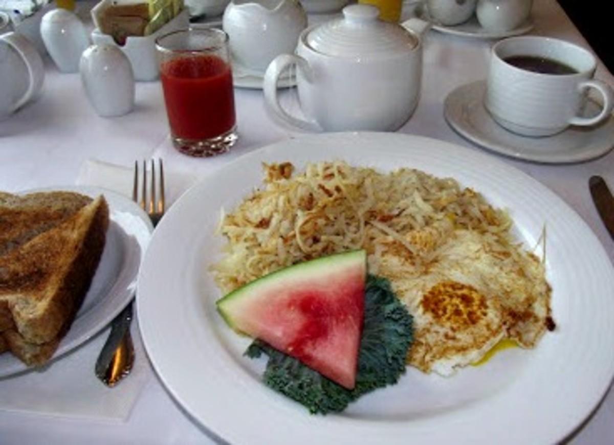 fried eggs, hashbrowns, toast, tomato juice and tea