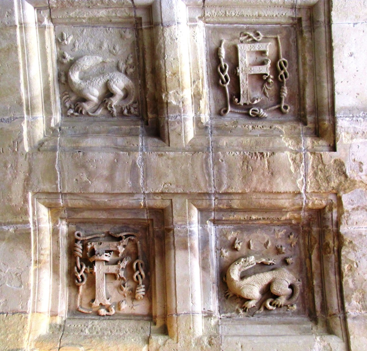 Ornate carvings of salamanders and the king's initial on the ceiling of the third floor.