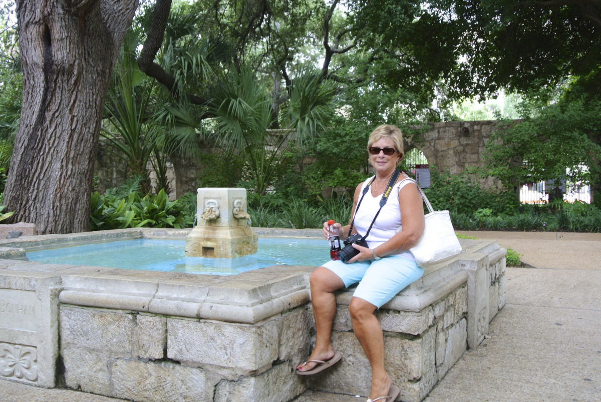My mom sitting near a fountain on the grounds of the Alamo