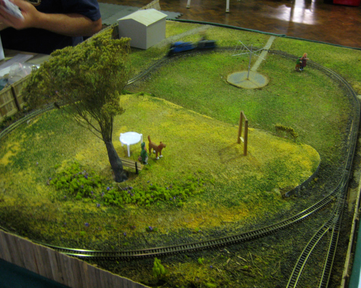 Bill's Backyard is O gauge figures riding on an N gauge train in a suburbian backyard complete with Hills Hoist.