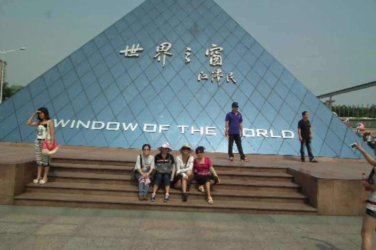 A family enjoying a day out at Window of the World, Shenzhen, South China. That's a replica of the Louvre, Paris, France in the background.