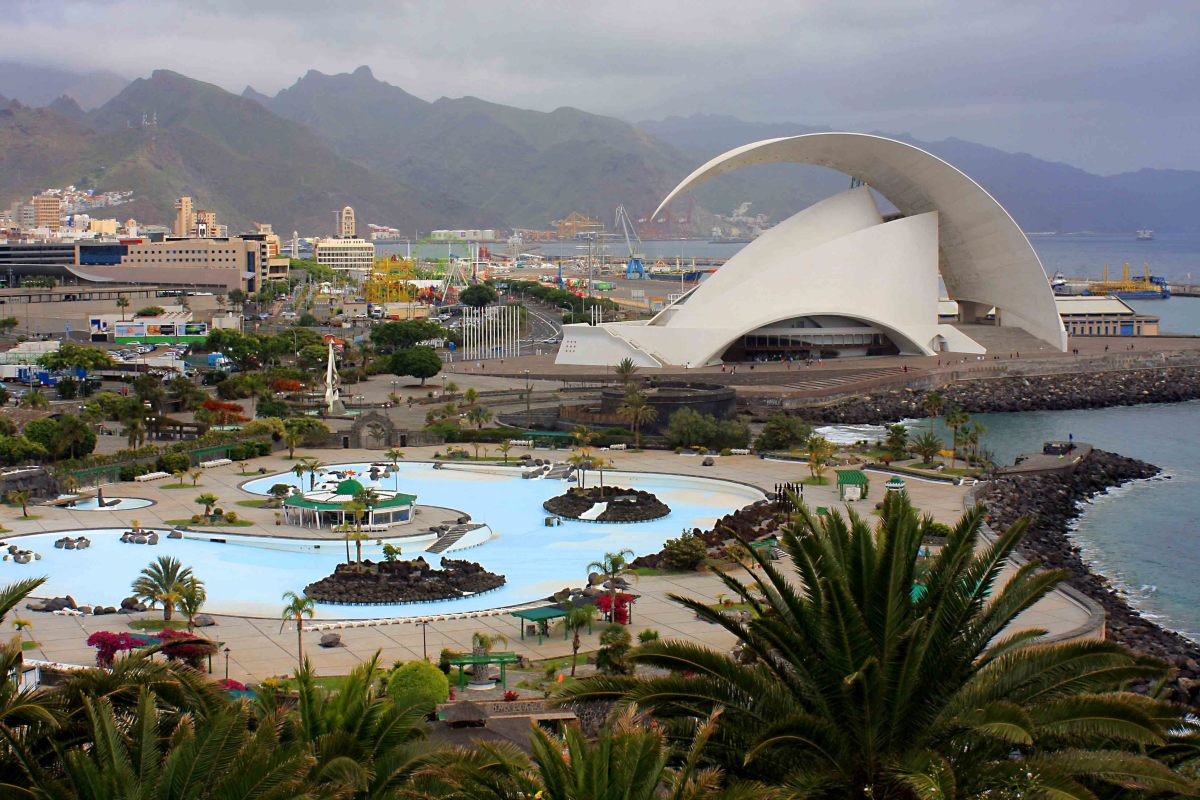 The mountains of Anaga, the Parque Maritimo Cesar Manrique and the distinctive architecture of the Tenerife Auditorium, with Palmetum palms in the foreground