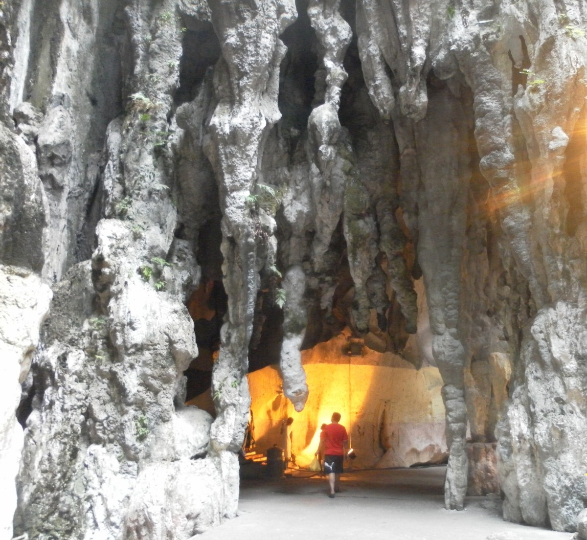 Rock formations inside Batu Caves. A small shrine stands in the lighted corner.