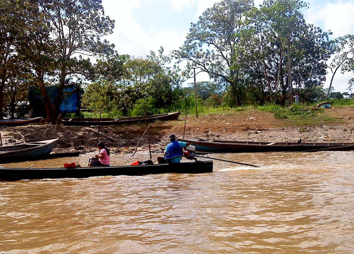 Fisherman and his wife about their business in a typical Amazon fishing boat.