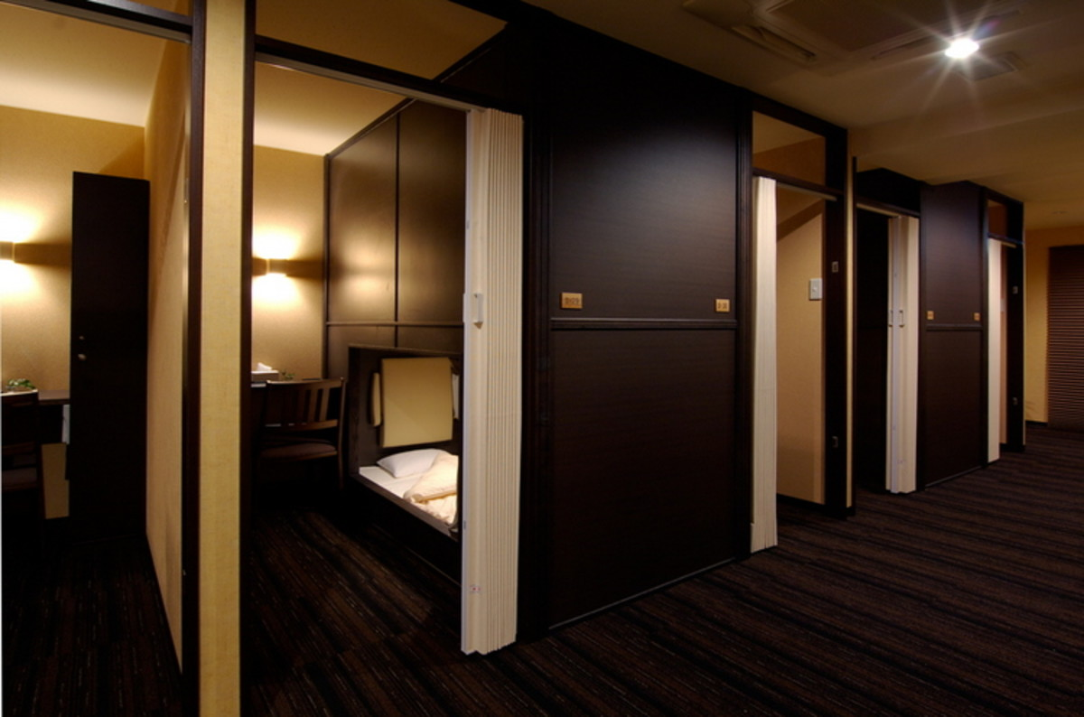 """At Well Cabin Nakasu, private """"cabins"""" (capsules) are available with a compact personal space and a sliding screen door for added privacy."""