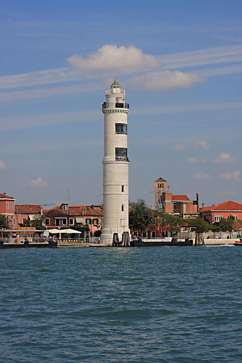 The Murano Lighthouse and the Faro Vaporetto Station. In the distance is the bell tower of Santi Maria e Donato