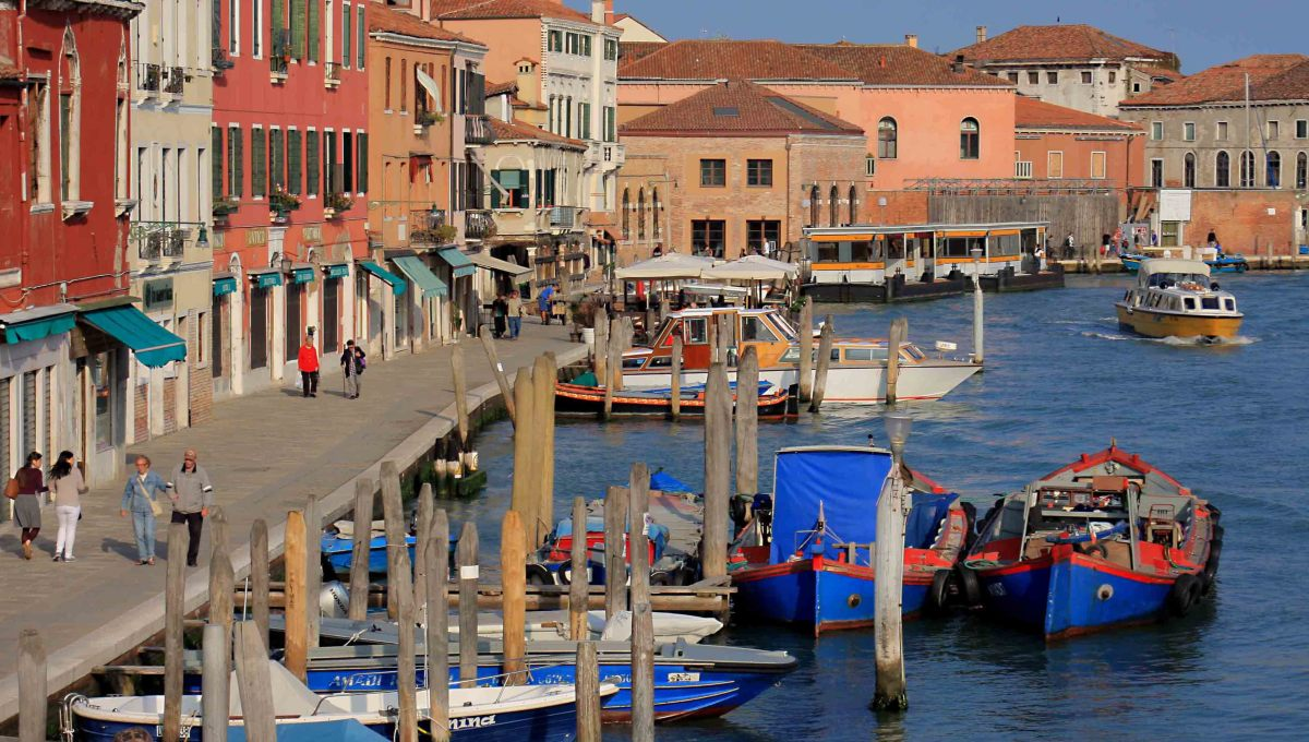 The pavements of Murano are lined with cafes and restaurants, souvenir shops and - of course - numerous ornamental glass retail outlets. This waterway is the Canale Ponte Lungo. In the distance is the vaporetto water bus station of Murano Museo
