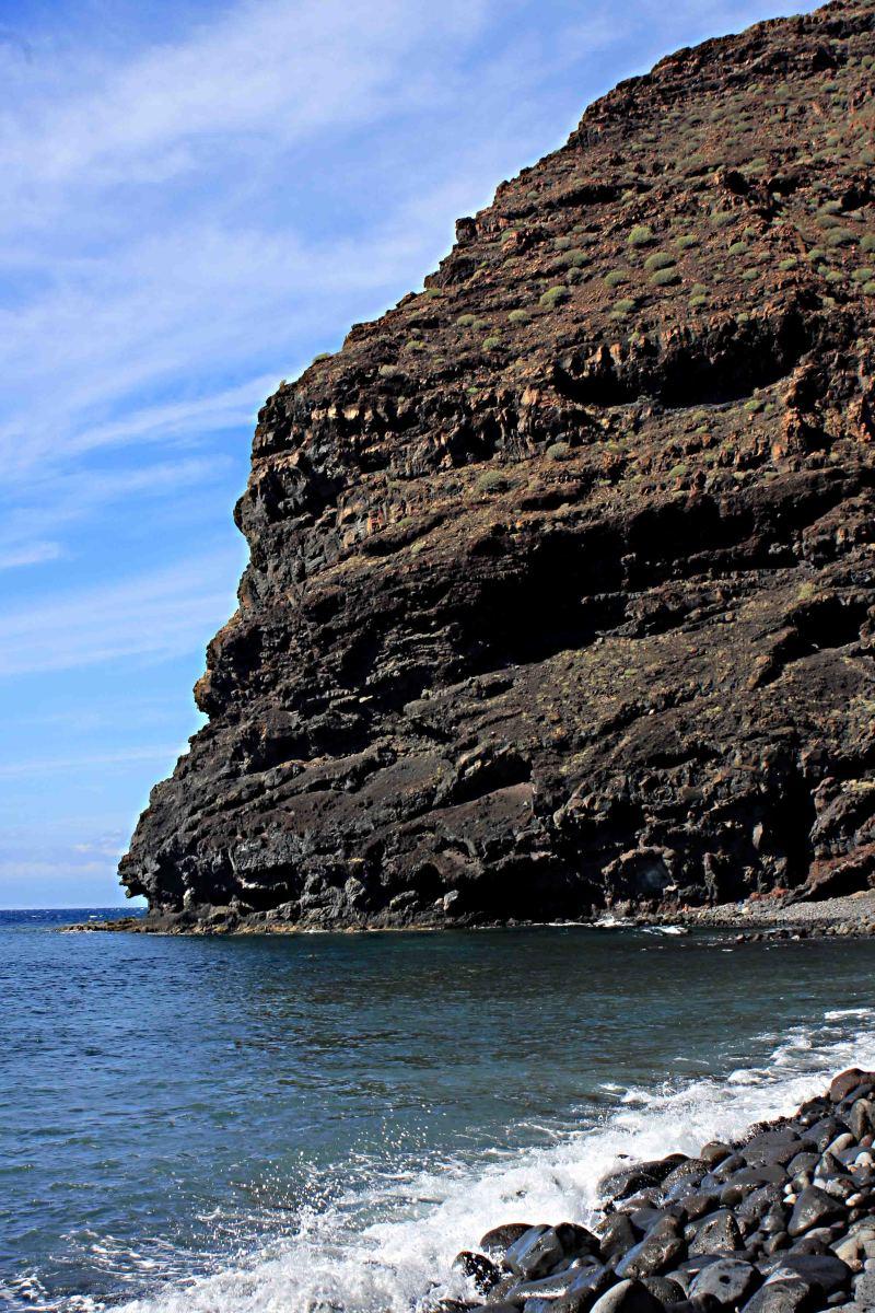 Even on a west coast beach, mountainous cliffs are never far away