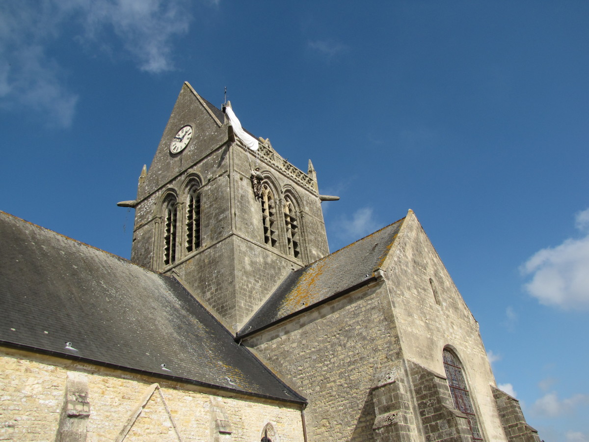 The church in Saint-Mere-Eglise where US paratrooper John Steele was caught in the church steeple.  If you look closely you can see a parachute and dummy marking the spot.