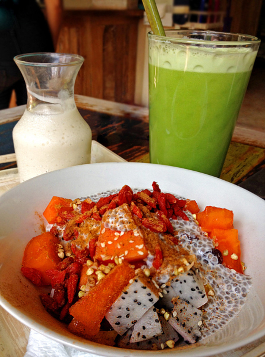 Cereal bowl of tropical fruits, goji berries, chia seeds, with vegan yogurt and green veggie juice.