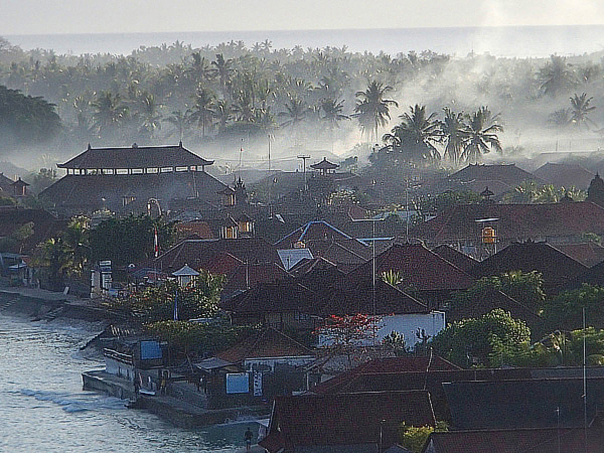 Smoke rises (from incense offerings) from homes and temples in early morning.