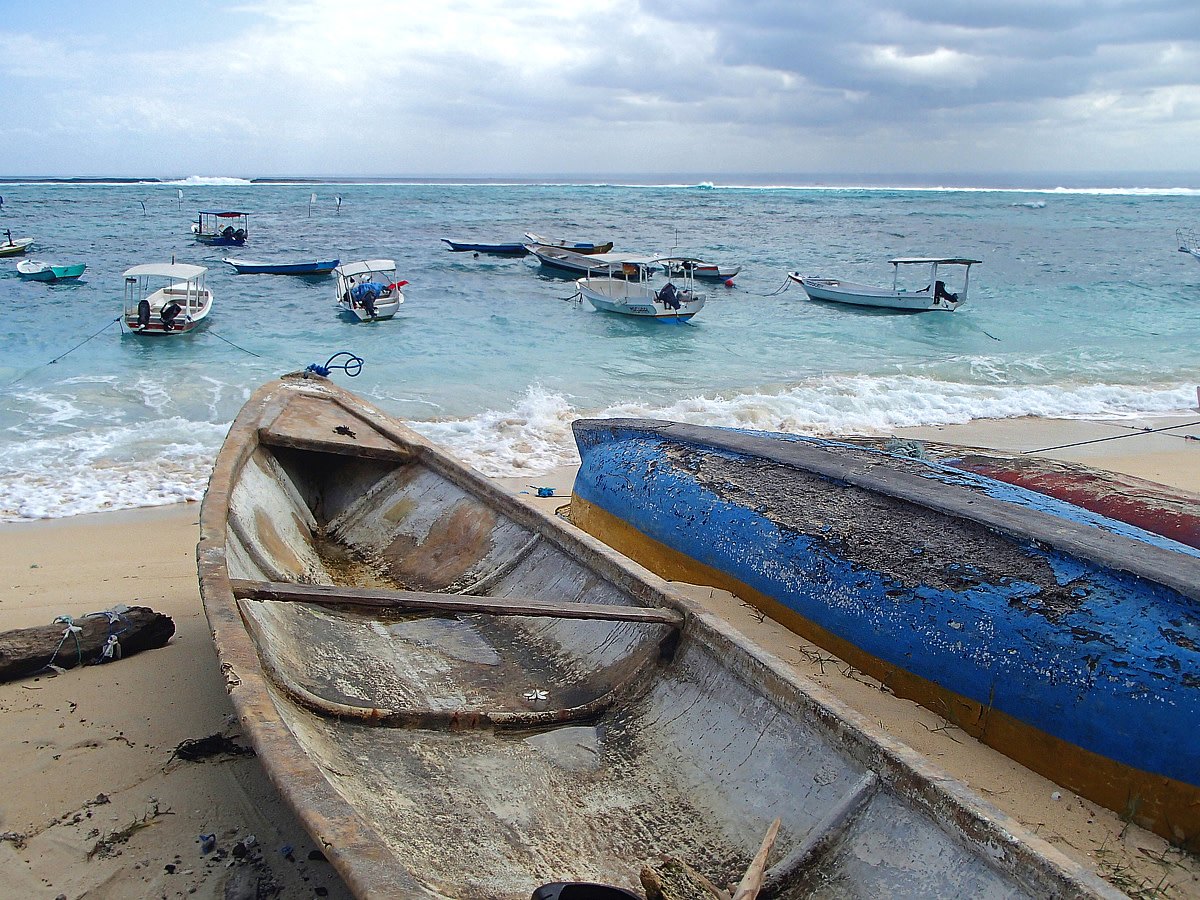 Old  fishing boats resting on shore.