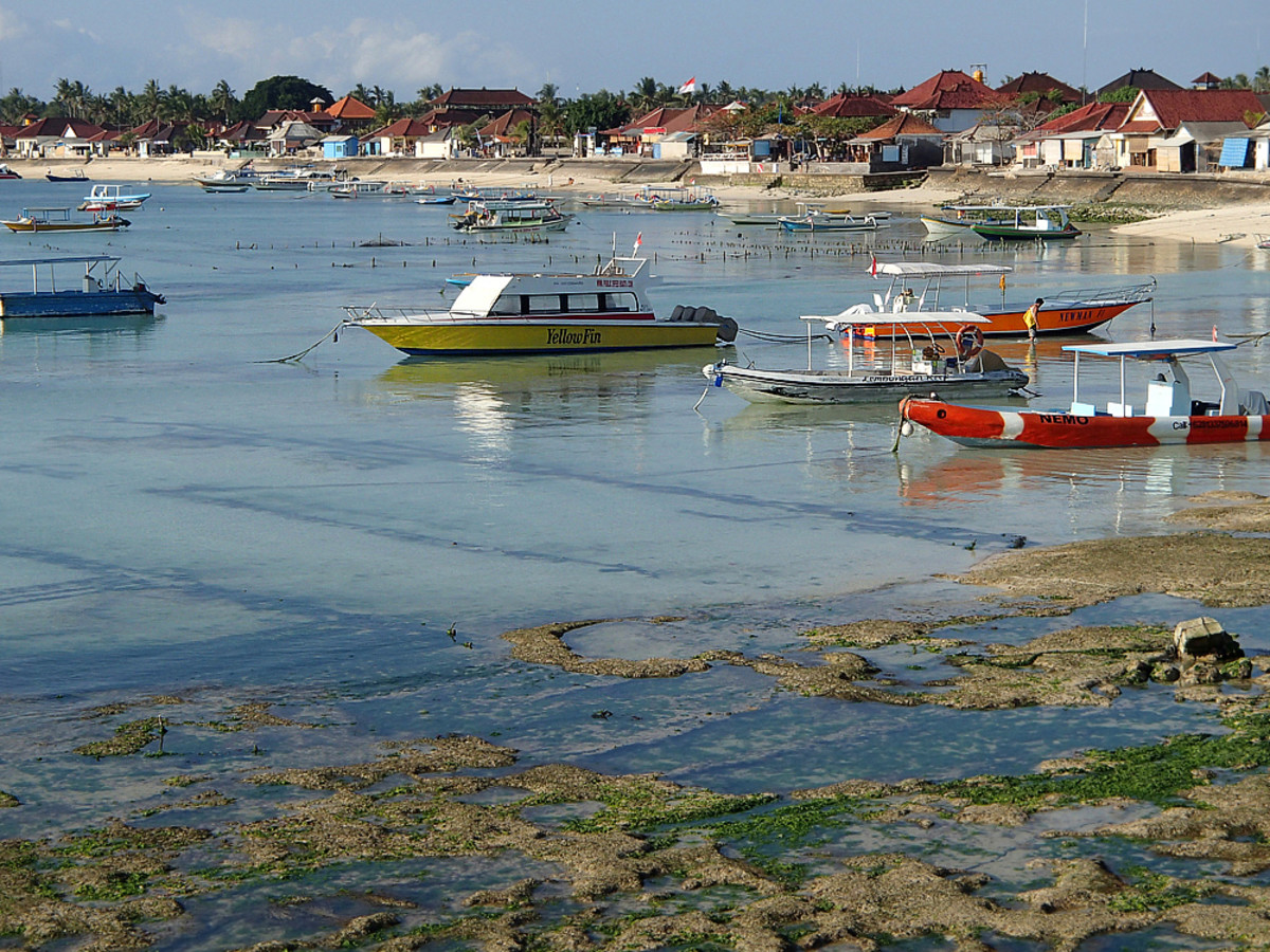 The sea slowly recedes during afternoon low tide, leaving boats sitting in a few inches of water.