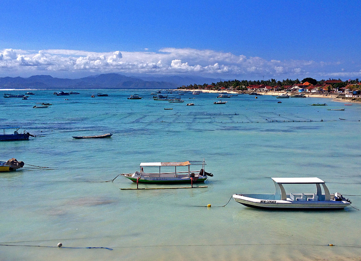 Calm blue water off the beachfront.  Mainland Bali can be seen in the horizon with clouds.