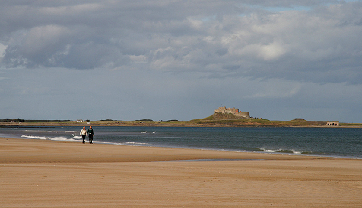 A couple walk along the shoreline with Lindisfarne Castle on Holy Island in the background.