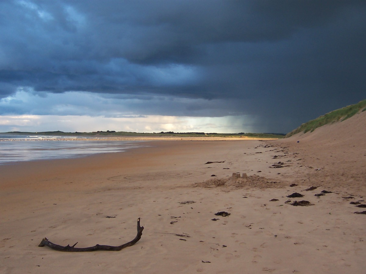 The Sandy beaches of Beadnell Bay under an evening sky