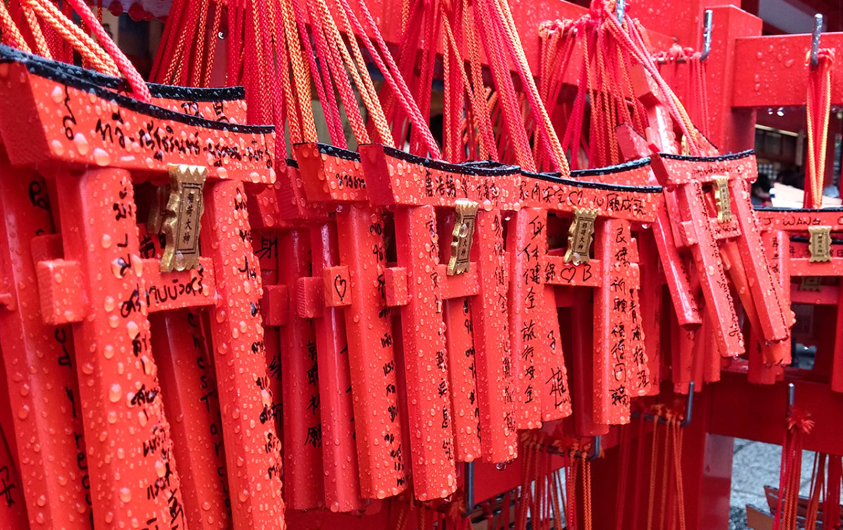 Drenched torii offerings at Fushimi Inari Shrine during a bad weather day.
