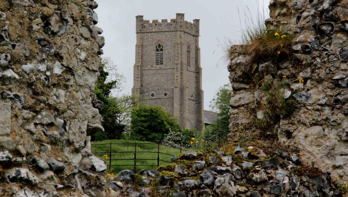 The stonework of the 12th century Castle Acre Priory, and in the distance the 15th century Church of St James the Great