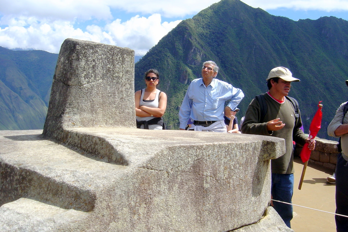 """Tourists admiring the handiwork of the Inca workmen who created the so-called """"compass rock,"""" whose points are lined up with the points of a compass, including one which is apparently aligned with magnetic north."""